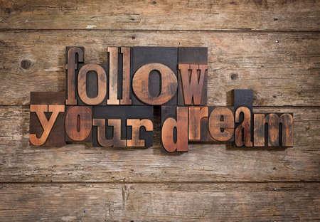 letterpress blocks: follow your dream, phrase set with vintage letterpress printing blocks on rustic wooden background