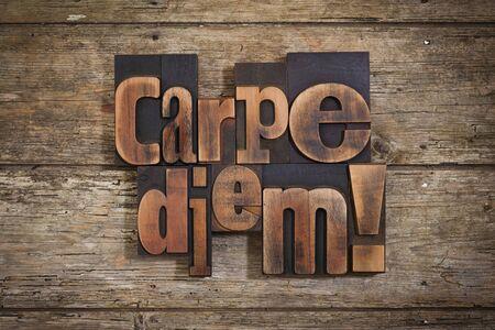 carpe diem: carpe diem, phrase set with vintage letterpress printing blocks on rustic wooden background