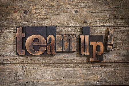 letterpress blocks: team up, phrase set with vintage letterpress printing blocks on rustic wooden background