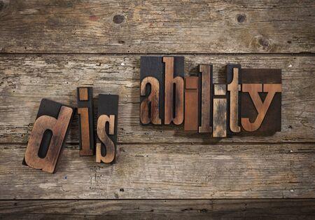 letterpress blocks: disability, split word set with vintage letterpress printing blocks on rustic wooden background,
