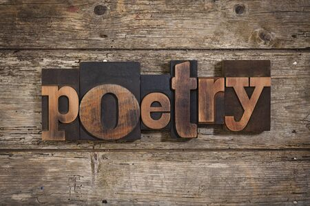 single word: poetry, single word set with vintage letterpress printing blocks on rustic wooden background