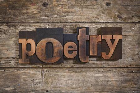 letterpress blocks: poetry, single word set with vintage letterpress printing blocks on rustic wooden background