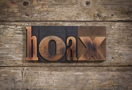 hoax: hoax, single word set with vintage letterpress printing blocks on rustic wooden background
