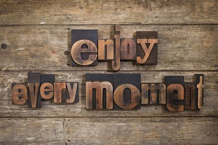 letterpress blocks: enjoy every moment, phrase set with vintage letterpress printing blocks on rustic wooden background