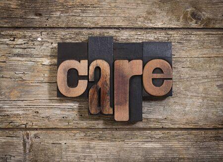 letterpress blocks: care, single word set with vintage letterpress printing blocks on rustic wooden background Stock Photo