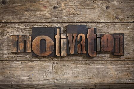 letterpress blocks: motivation, single word set with vintage letterpress printing blocks on rustic wooden background