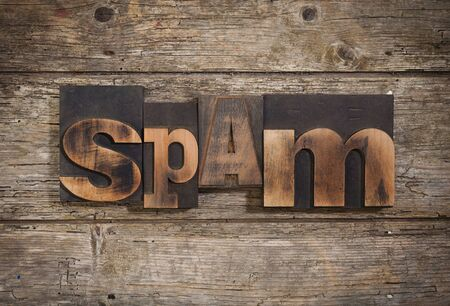 letterpress blocks: spam, single word set with vintage letterpress printing blocks on rustic wooden background Stock Photo