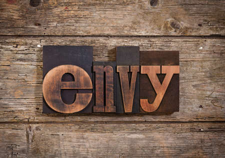 envy: envy, single word set with vintage letterpress printing blocks on rustic wooden background