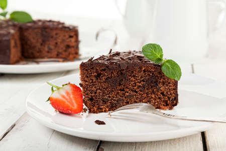 porcion de torta: Closeup of piece of chocolate cake with strawberry on coffee table