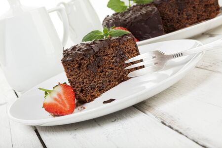 tilted: Chocolate cake and strawberry on coffee table, tilted view Stock Photo