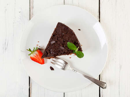 high angle view: Piece of chocolate cake and strawberries on a plate, high angle view