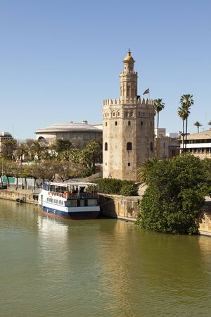fortify: Ancient lighthouse Torre del Oro at Seville, a tourist boat anchored at the pier Stock Photo