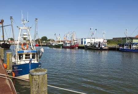towed: Büsum, Germany - July 20, 2016: Fishing boats towed at the piers of Buesum fishing harbor.