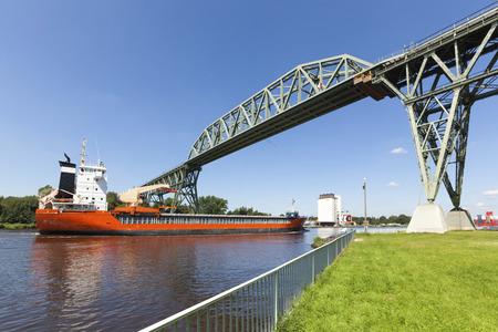 kiel: Freight ship passing historic Hochdonn railway bridge on Kiel Canal