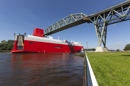 car carrier: A huge car carrier passing the historic railway bridge crossing Kiel Canal at Hochdonn
