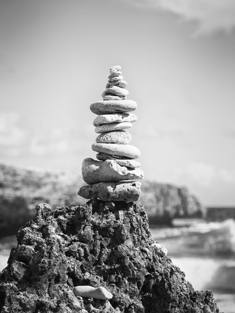 high stack of pebbles on a pointed rock at the ocean, black and white image Stock Photo