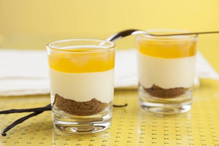 dessert topping: Two glasses filled with a dessert made of cream, cake, mango topping on glass table