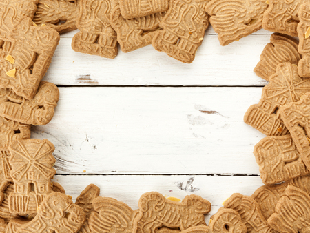 speculaas: Image border of dutch speculaas cookies on white rustic wooden background