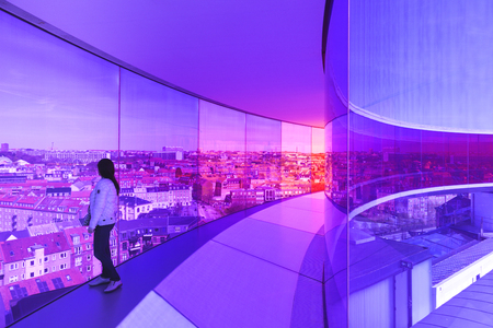 Aarhus, Denmark - May 2, 2017: Young woman inside Olafur Eliassons installation on top of the art museum, viewing over the city through purple tinted window