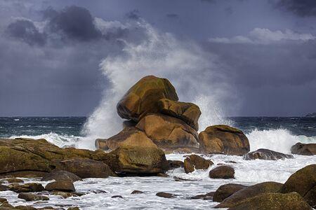 Rock in the surf breaking a huge wave