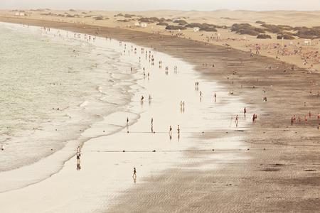 Mensen bij het Playa del Ingles-strand, Grote Kanarie, Duinen van Maspalomas op achtergrond