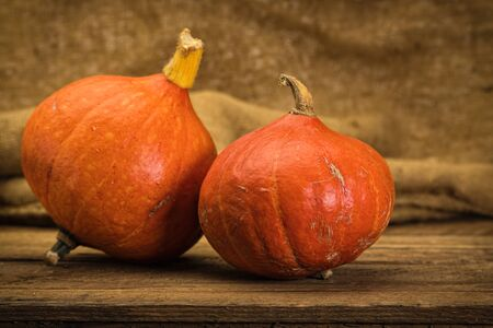 Red Kuri squashes on rustic wooden table Foto de archivo - 130503994