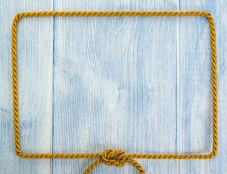 Frame of golden rope on rustic blue wooden background Foto de archivo - 130431123