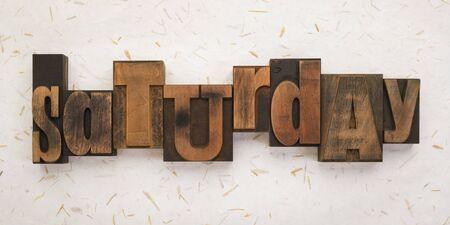 Saturday, word written with vintage letterpress printing blocks on textured background . Banner format.