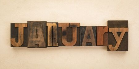 January, name of the month written with vintage letterpress printing blocks on textured background . Banner format.