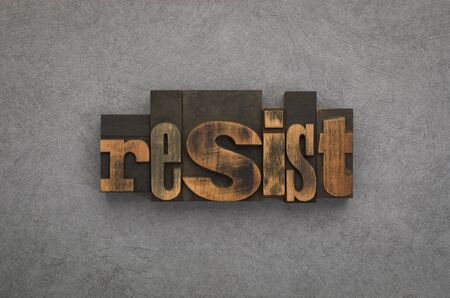 Resist, single word written with vintage letterpress printing blocks on textured grey background.