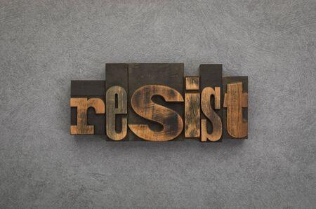Resist, single word written with vintage letterpress printing blocks on textured grey background.