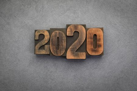 Year 2020 written with vintage letterpress printing blocks on grey textured background