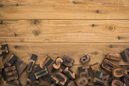 Rustic wooden background with random vintage letterpress printing blocks at bottom