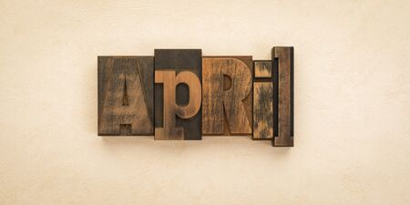 April, name of the month written with vintage letterpress printing blocks on textured background . Banner format.