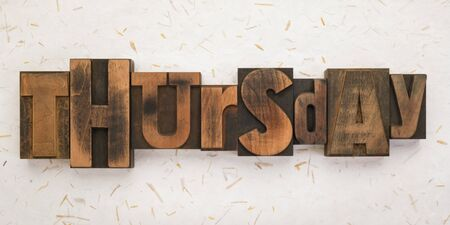 Thursday, word written with vintage letterpress printing blocks on textured background . Banner format.