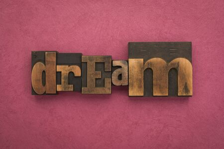 Dream, single word written with vintage letterpress printing blocks on textured pink background.