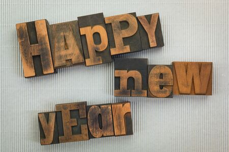 Happy new year , phrase written with vintage letterpress printing blocks on silver textured background Фото со стока