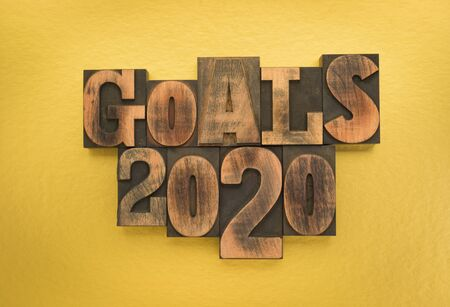 Goals 2020, phrase written with vintage letterpress printing blocks on gold colored background