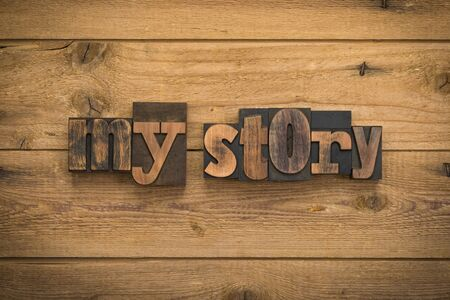 My story, phrase written with vintage letterpress printing blocks on rustic wood background.