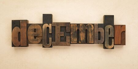 December, name of the month written with vintage letterpress printing blocks on textured background . Banner format.
