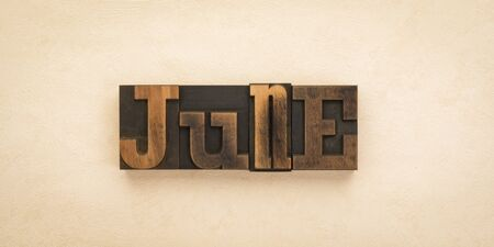 June, name of the month written with vintage letterpress printing blocks on textured background . Banner format.