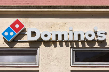 Stade, Germany - May 28, 2020: Signage outside a Dominos Pizza outlet. Domino's Pizza, Inc., branded as Domino's, is an American multinational pizza restaurant chain founded in 1960