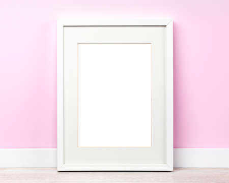 Poster mockup with white picture frameleaning on pink wall. Artwork template, blank area isolated with clipping path. 免版税图像
