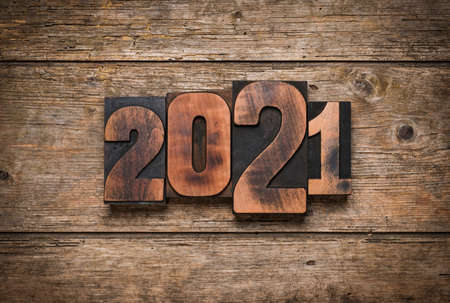 Year 2021 written with vintage letterpress printing block numbers on rustic wooden background