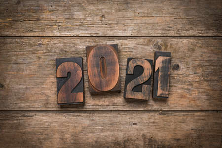 Year 2021 set loosely with vintage prining blocks on rustic wooden background