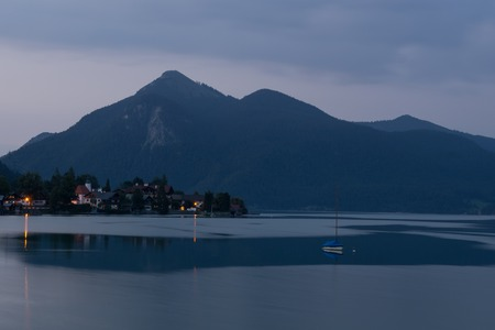 German alp sea at blue hour with boat, city, mountain and reflection