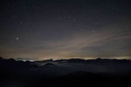 Clouds rolling over the mountains of the alps at night time with a starry sky and the constellation Big Dipper Banco de Imagens