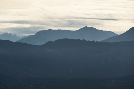 Mountain silhouettes with forest and cloudy sky