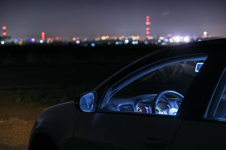 Car at night in front of city skyline