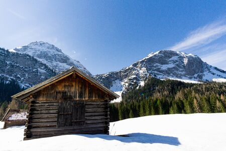 Alpine wooden cabin in snow in front of mountains with trees and blue sky 版權商用圖片